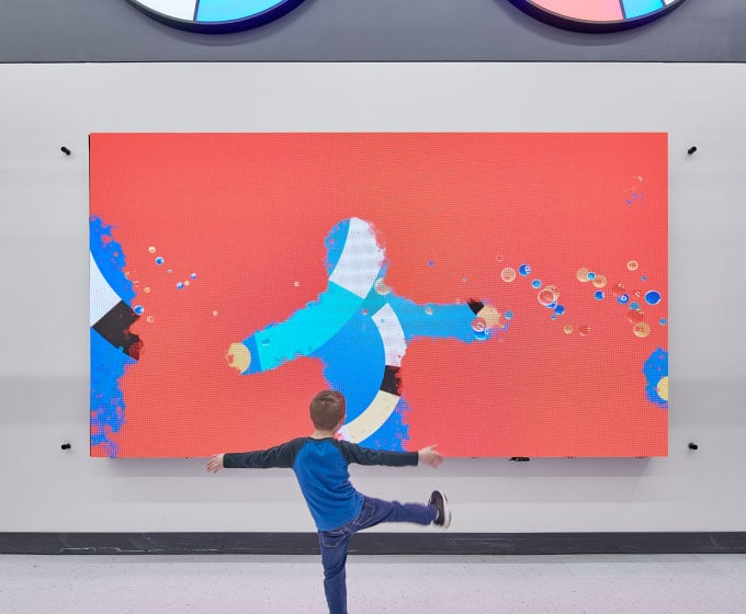 A kid lifts his feet high up in front of the AI interactive wall. Image via Walmart