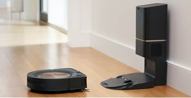 The vacuum cleaner sits in front of cleaning base station. Image via iRobot