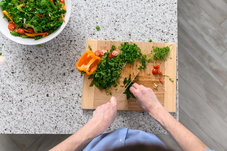 A person cuts the vegetables on the chopping board. Image via OGarden